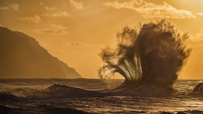 Two waves crashing into each other during a Hawaiian sunset