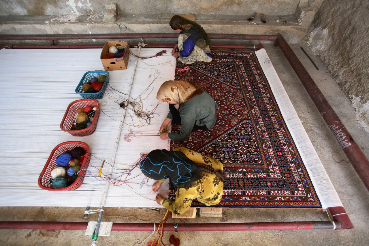 Weaving a carpet by hand in Iran