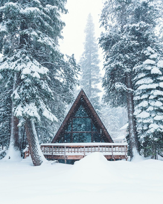 Snow falls thick on a cabin in the woods