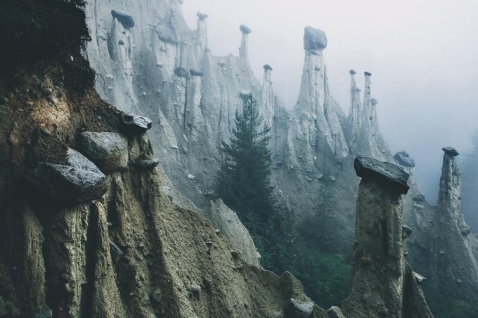Rocks perched on eroded pillars of dirt in the alps of Italy